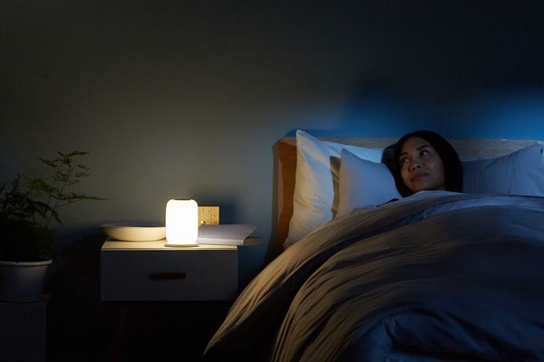 Women laying in bed at night with her Casper glow light