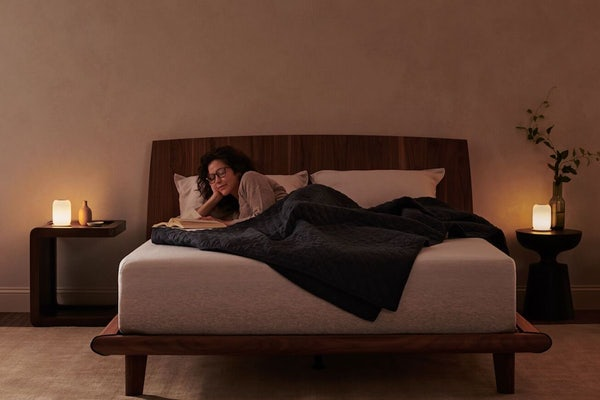 Woman relaxing on her Casper mattress in a dim room with glow lights