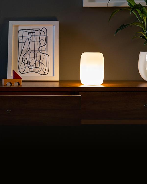 glow light next to art print on dresser in dim room