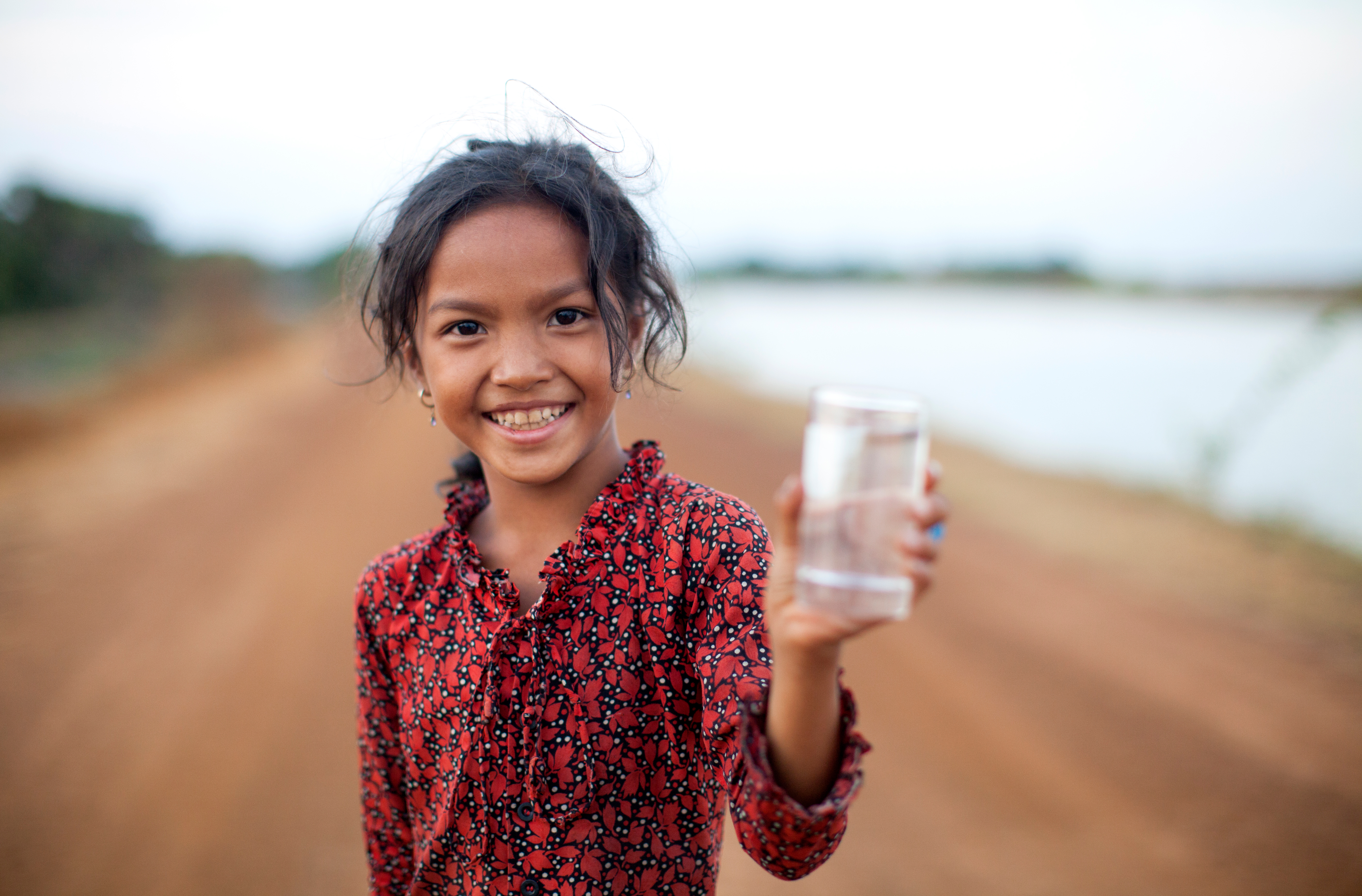 Smiling girl holds glass of water