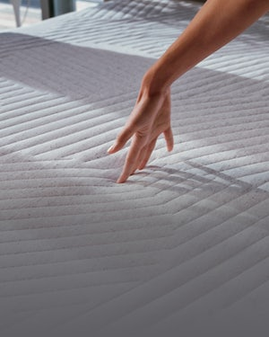 Fingertips pressing into the QuickCool layer of the Nova Hybrid Snow mattress.